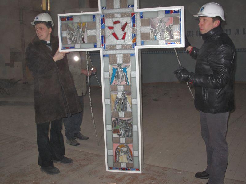 Abiõpetaja Kristjan Luhamets ja Nordecon Ehituse projektijuht Peeter Voovere võtavad vastu alla lastud vitraažristi. Rita Puidet
